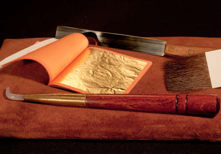 a booklet of pure gold leaf for gilding with craftsman's tools Stockfoto