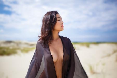 Giovane ragazza asiatica nuda con un panno nero nel deserto