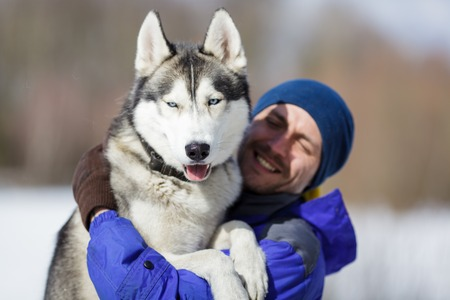 necking: Happy man with a husky at winter time
