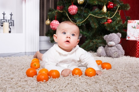 6 12 months: Little baby lying with tangerine on the christmastree background