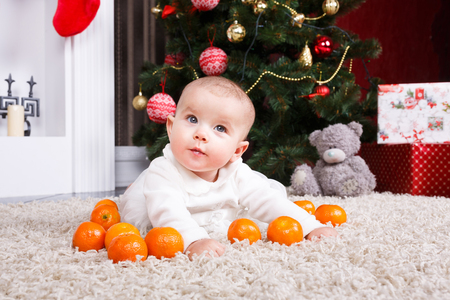 0 1 months: Little baby lying with tangerine on the christmastree background
