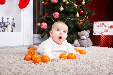 0 6 months: Little baby lying with tangerine on the christmastree background