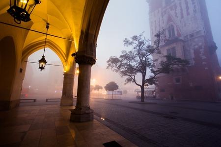 朝の霧、ポーランドのクラクフの市場広場のアーチします。