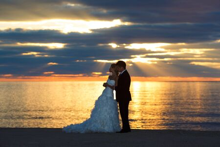 Young couple of sweethearts hugging along the seacoast photo