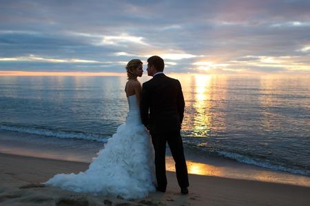 海岸沿いを抱いての恋人の若いカップル