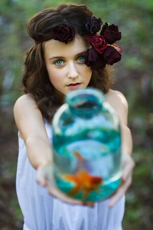 gold fish: Young girl with gold fish at summer time