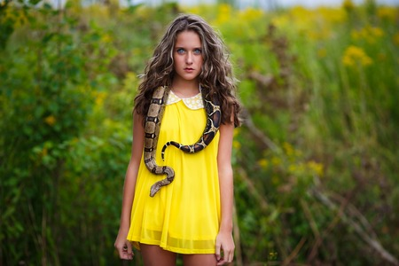animal eye: Beautiful young girl with snake in a park