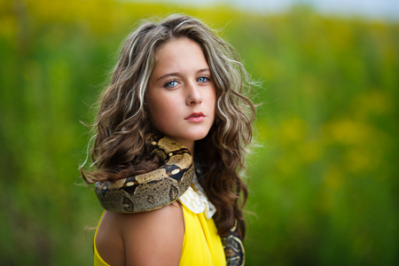 Beautiful young girl with snake in a park photo