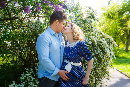 Young pregnant couple kissing in the garden photo