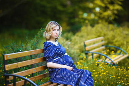 Young pregnant woman sitting on a bench in the park photo