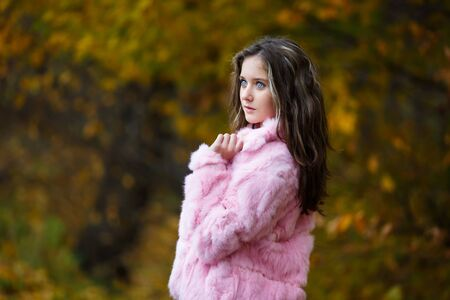 pink fur: Portrait of beautiful girl in a pink fur coat on a background of yellow leaves Stock Photo