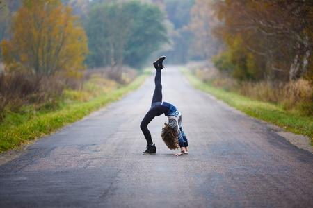 若いプロの体操選手は、秋時に道路上の分割