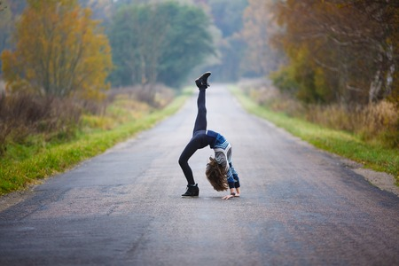 Young professional gymnast makes splits on the road at autumn time Stock Photo