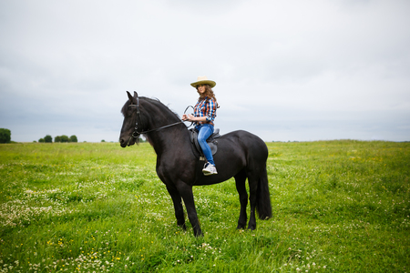 Beautiful young girl riding a horse in countryside at summer time Stock Photo
