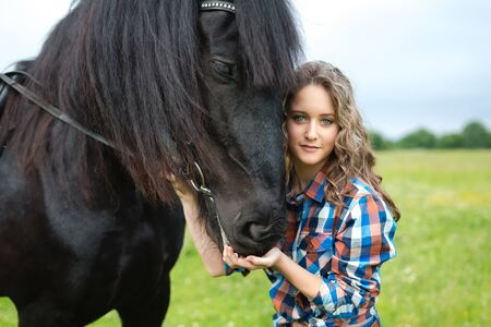 Young beautiful girl with frisian horse standing in the meadow at summer time Zdjęcie Seryjne - 37305997
