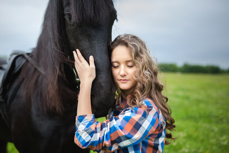 horses in field: Young beautiful girl with frisian horse standing in the meadow at summer time