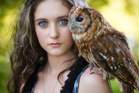 Portrait of beautiful young girl with owl in a forest at summer time