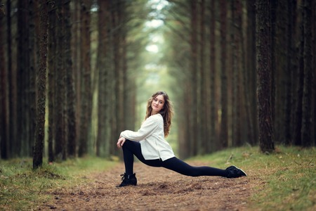 Young professional gymnast makes splits in the forest photo