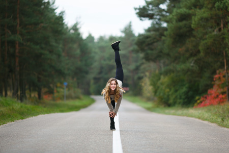 Young professional gymnast makes splits on the road at autumn time photo