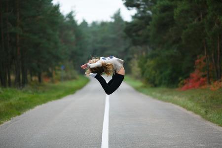 gimnasia ritmica: Gimnasta profesional joven que salta en la carretera en el oto�o de tiempo Foto de archivo