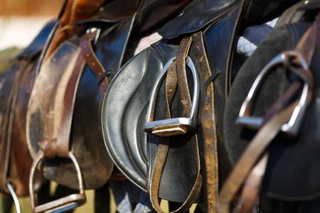 caballo: A sillas de montar que ponen en la cerca r�stica en luz del sol caliente Foto de archivo
