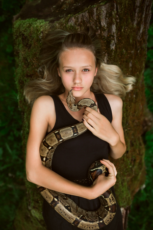 captivate: Portrait of a lying beautiful young girl with snake in a forest