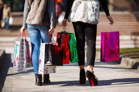 Two young women walking with shopping bags outdoor photo