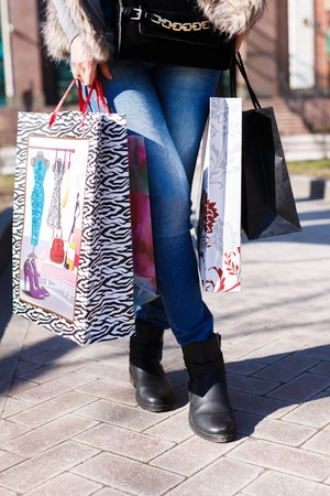 Young woman walking with shopping bags outdoor photo