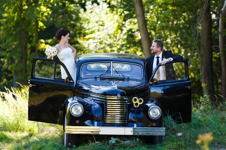 幸せな結婚式カップル背景古い車の上に立っています。 写真素材