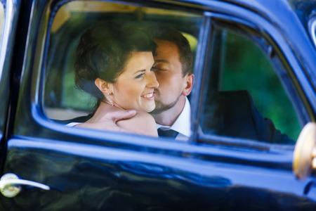 Embrace happy wedding couple inside old car photo