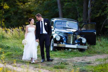 背景の古い車の上の結婚式のカップルを歩く