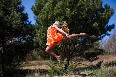 Young gymnast doing exercises in a forest at spring time photo