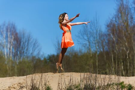 mastery: Young gymnast doing exercises in a forest at spring time