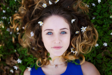 Portrait of a beautiful girl with flowers in her hair at spring time