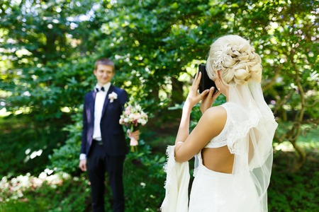 Bride shooting of her fiance in a park Stock Photo