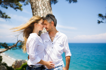 blondie: Happy couple hugging on the seacoast in the shadow of pine tree Stock Photo