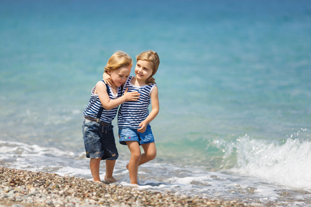 beautiful little boys: Little brother and sister walking on the beach