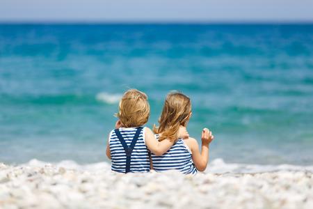 弟と妹は、ビーチの上を歩く 写真素材