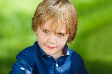 grandkids: Portrait of a little cute boy on the green background Stock Photo
