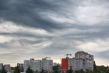lurid: Dark clouds asperatus before the storm over city Stock Photo
