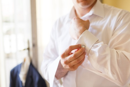 businesswear: Man puts cufflinks on sleeve white shirts
