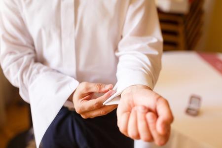 businesswear: Man puts cufflinks on sleeve white shirts
