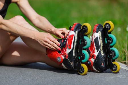rollerblade: Young girl sitting on the ground and putting on inline skates