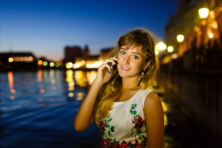 conversa: Pretty young girl talks on mobile phone in the night city