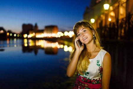conversaciones: Bastante joven muchacha habla en el teléfono móvil en la ciudad de noche