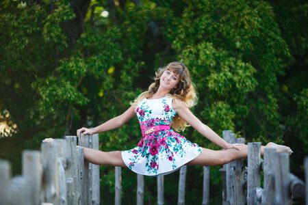 the split: Attractive young girl doing split exercises on the wooden fence Stock Photo