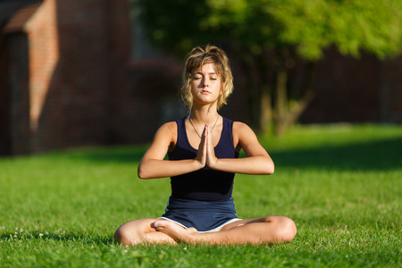 natural health and beauty: Pretty young girl doing yoga exercises in the park Stock Photo
