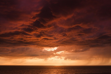 red sky: Thundercloud on the background of sunset over the Baltic Sea