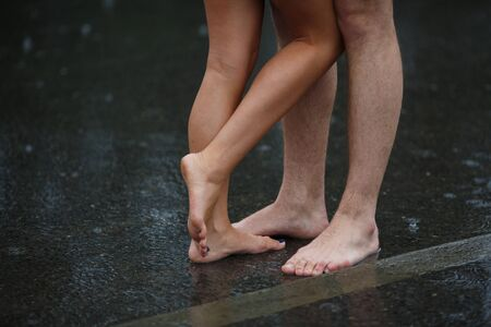 young woman nude: Legs of couple standing on the asphalt road in the rain Stock Photo