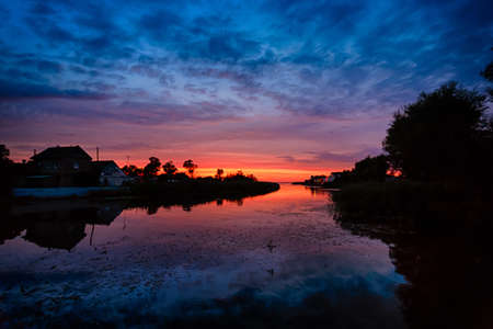 lurid: Beautiful sunset with incredible reflection at the summer time